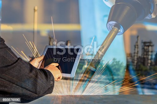 693576566 istock photo businessman is used smart phone control automate wireless Robot welding. It is industrial4.0 concept with double exposure 693576590