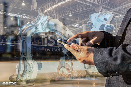 693576566 istock photo businessman is used smart phone control automate wireless Robot welding. It is industrial4.0 concept with double exposure 866887502