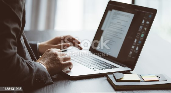 Businessman working on laptop and analysing the financial information at his office. Close up of male hands typing on computer keyboard