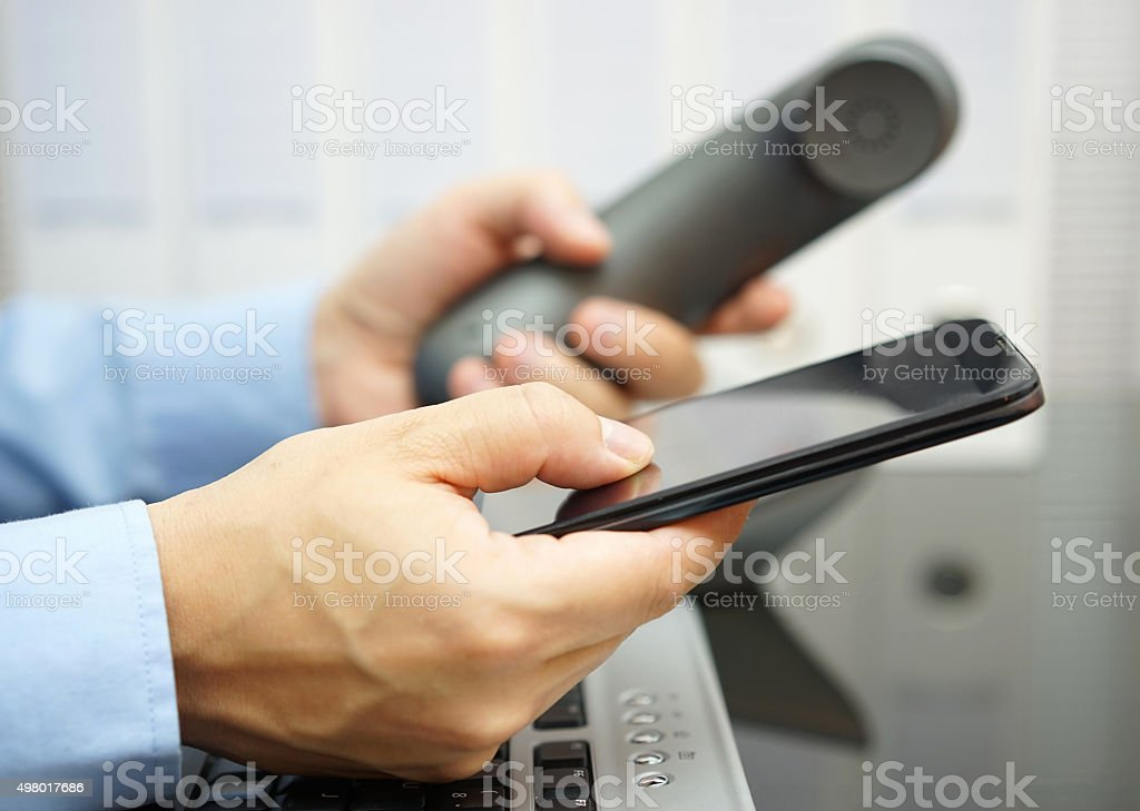 businessman is using  smart mobile phone and land line telephone stock photo
