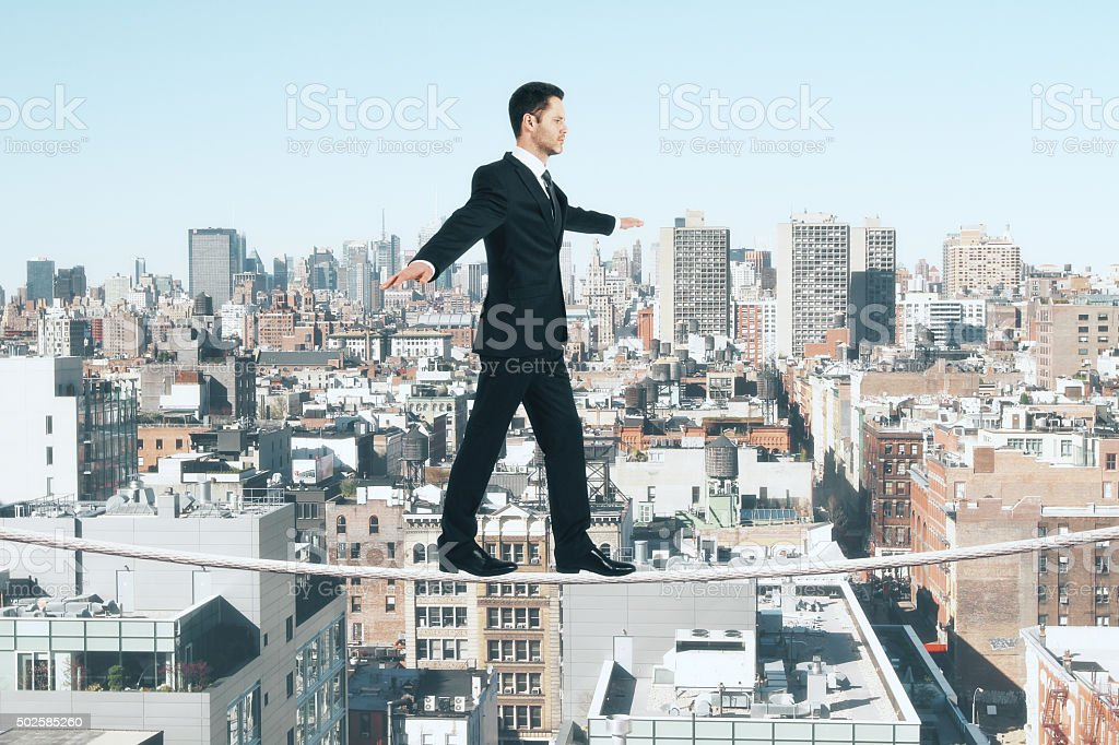 Businessman is walking on a rope at city background stock photo