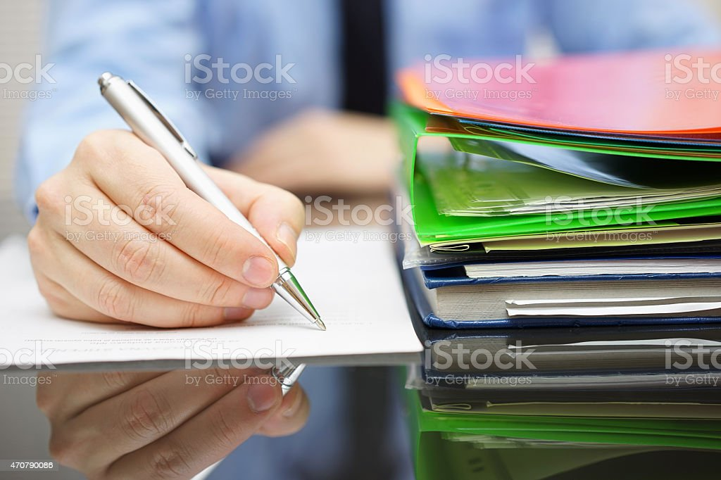 businessman is writing on document and lot of documentation stock photo