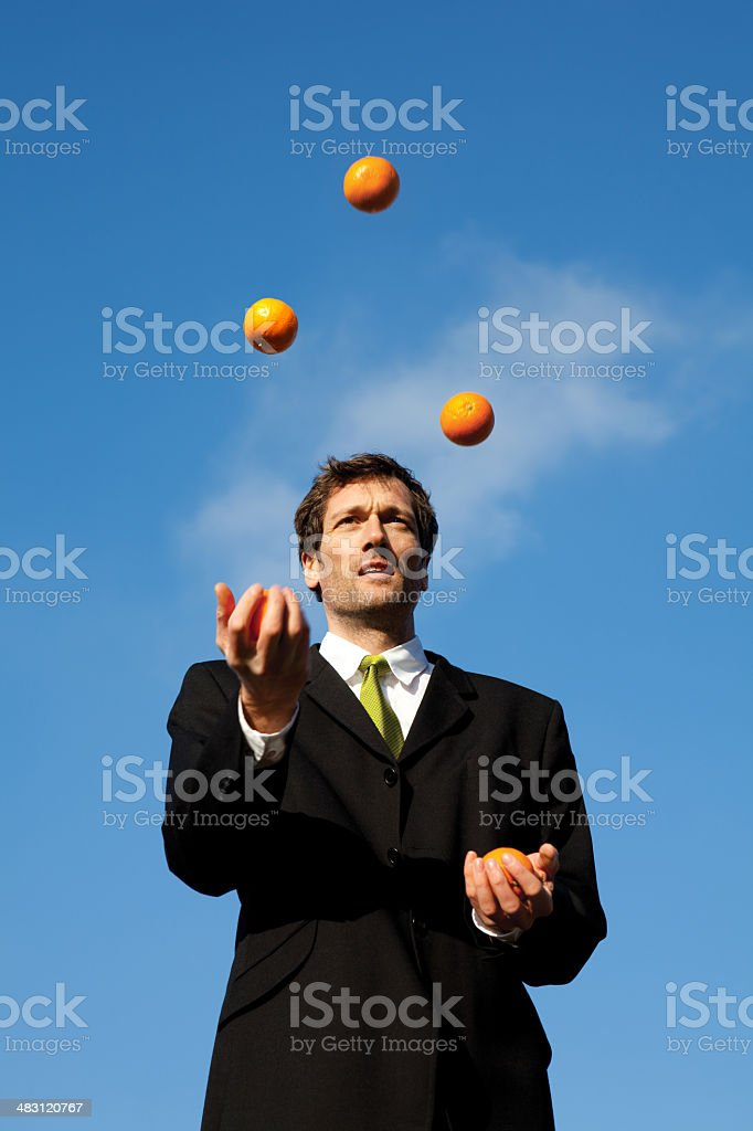 Businessman Juggling Oranges Outside royalty-free stock photo
