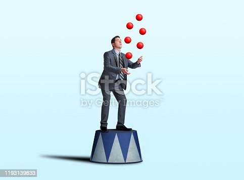 A businessman stands on a circus pedestal as he juggles a group of red balls isolated on a light blue background.