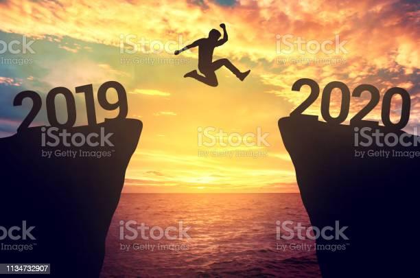 Businessman Jump Between 2019 And 2020 Years - Fotografias de stock e mais imagens de 2019