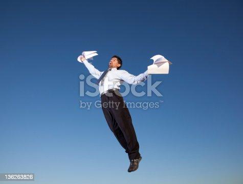 157312920 istock photo Businessman jump holding documents 136263826