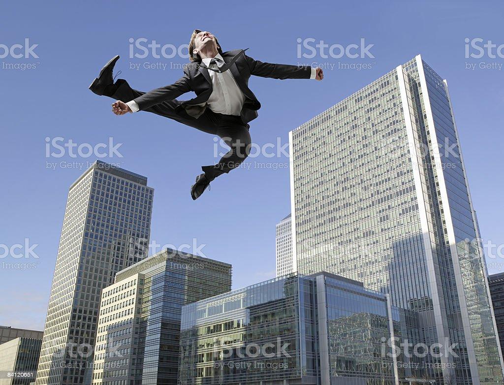 Businessman jumping above City scape foto de stock libre de derechos