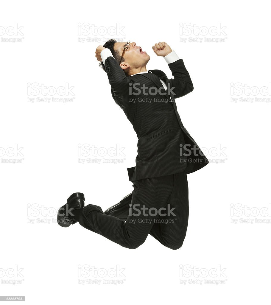 Businessman jumping and cheering with hand raised royalty-free stock photo