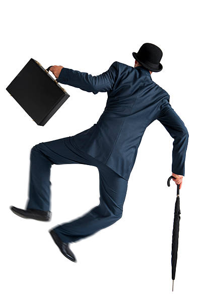 businessman jumping and kicking his heels isolated on white stock photo