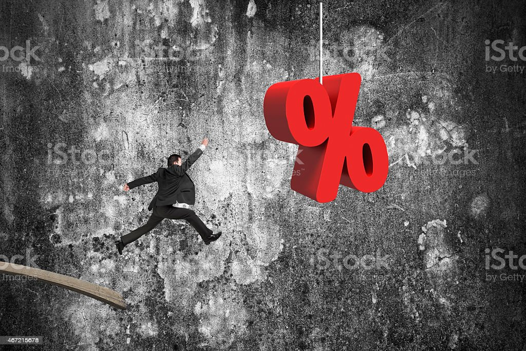 Businessman jumping from wooden board to red percentage sign stock photo