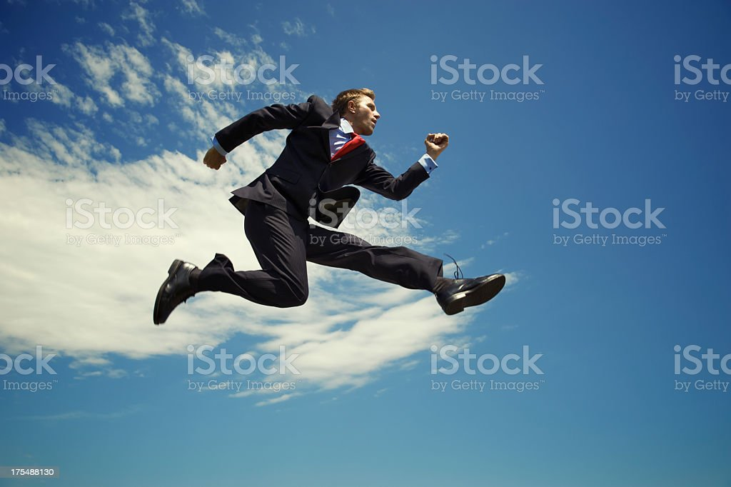 Businessman Jumping High Outdoors in Blue Sky with Clouds stock photo