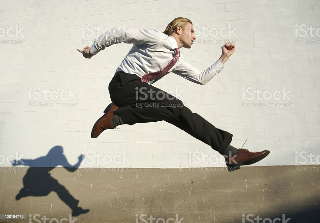 Businessman Jumping Outdoors Across White Wall with Shadow stock photo