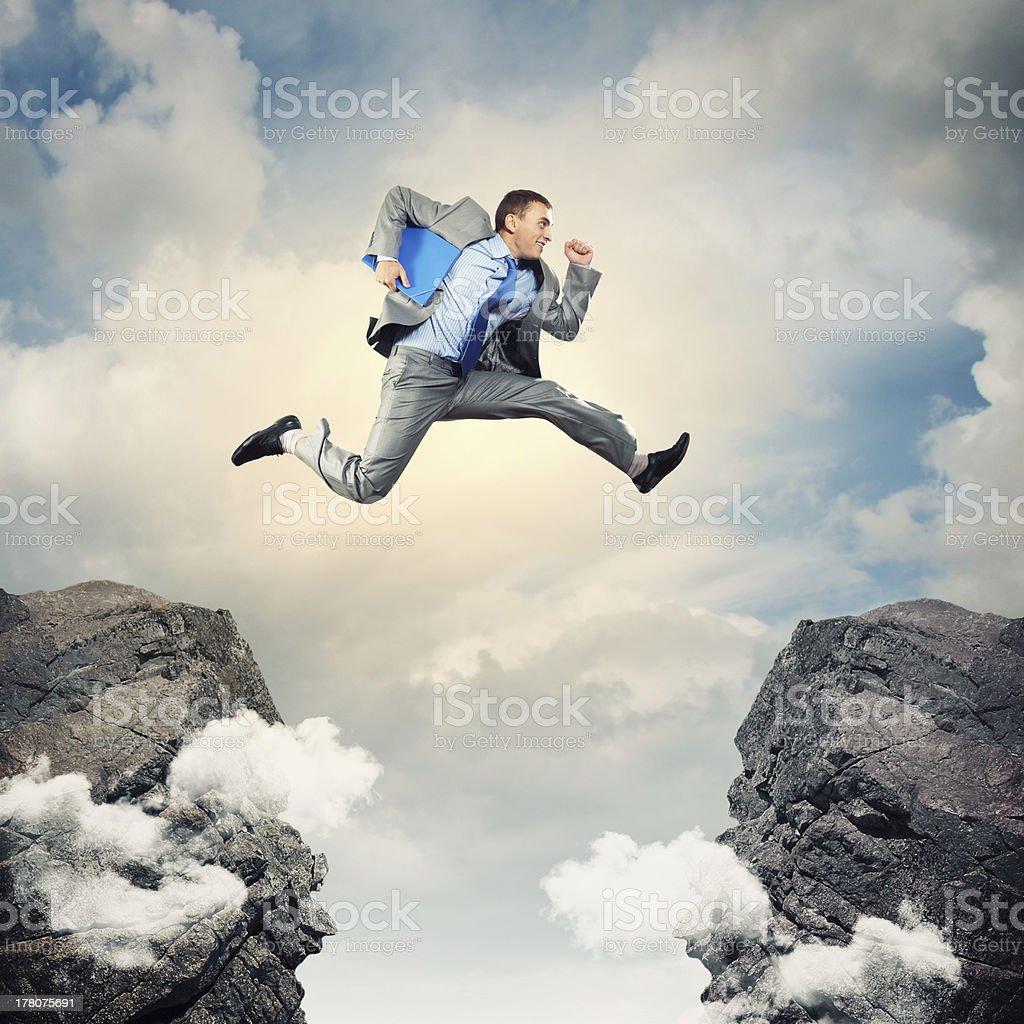 Businessman jumping over gap stock photo