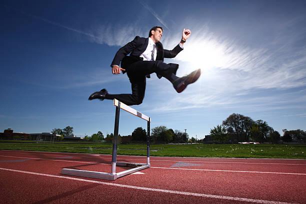 Empresário saltando sobre obstáculo - foto de acervo