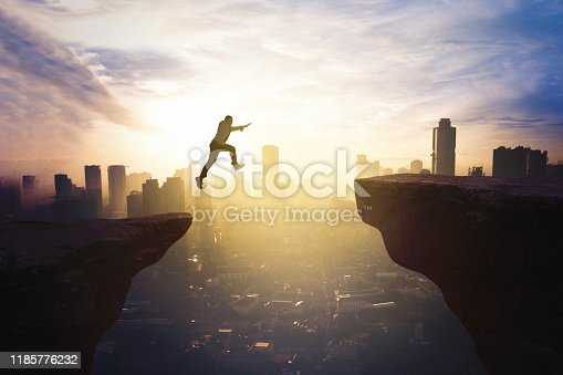 Young businessman jumping through gap cliff at sunrise time with modern city background