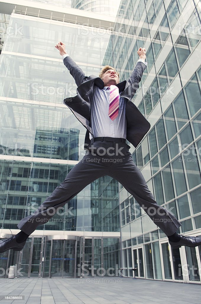 Businessman Jumps in front of Modern Glass Office Tower stock photo