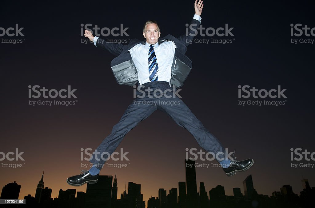 Businessman Jumps Over Sunset Skyline stock photo