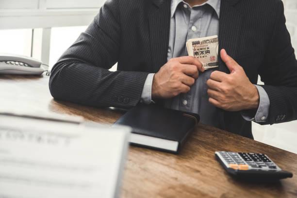 ビジネスマンがスーツのポケットに日本円のお金を保つ - 不正直 ストックフォトと画像