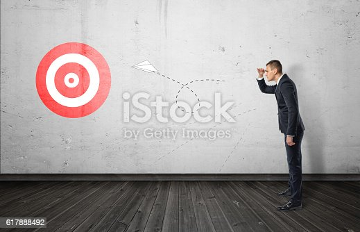 istock Businessman keeping track of the paper airplane flying right on 617888492