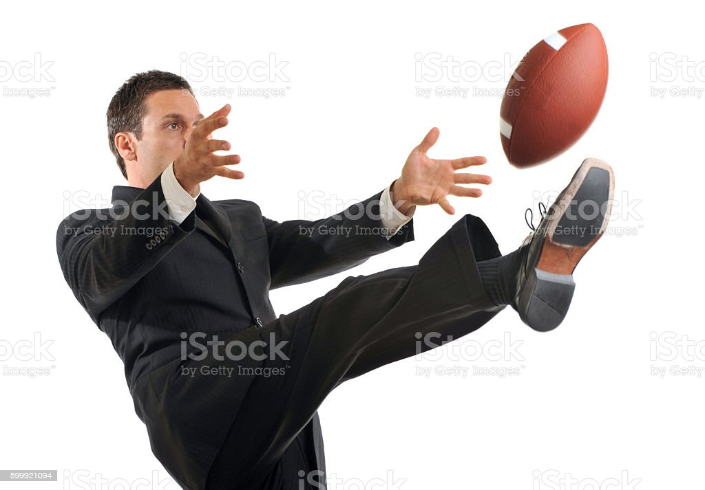 Businessman Kicking American Football on White stock photo