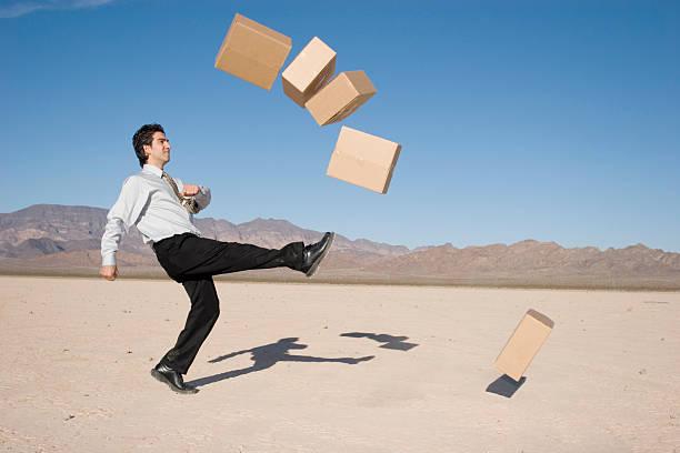 Businessman kicking boxes stock photo