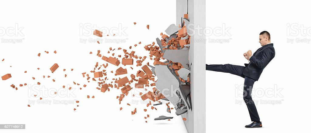 Businessman kicking hard the wall and crush it stock photo