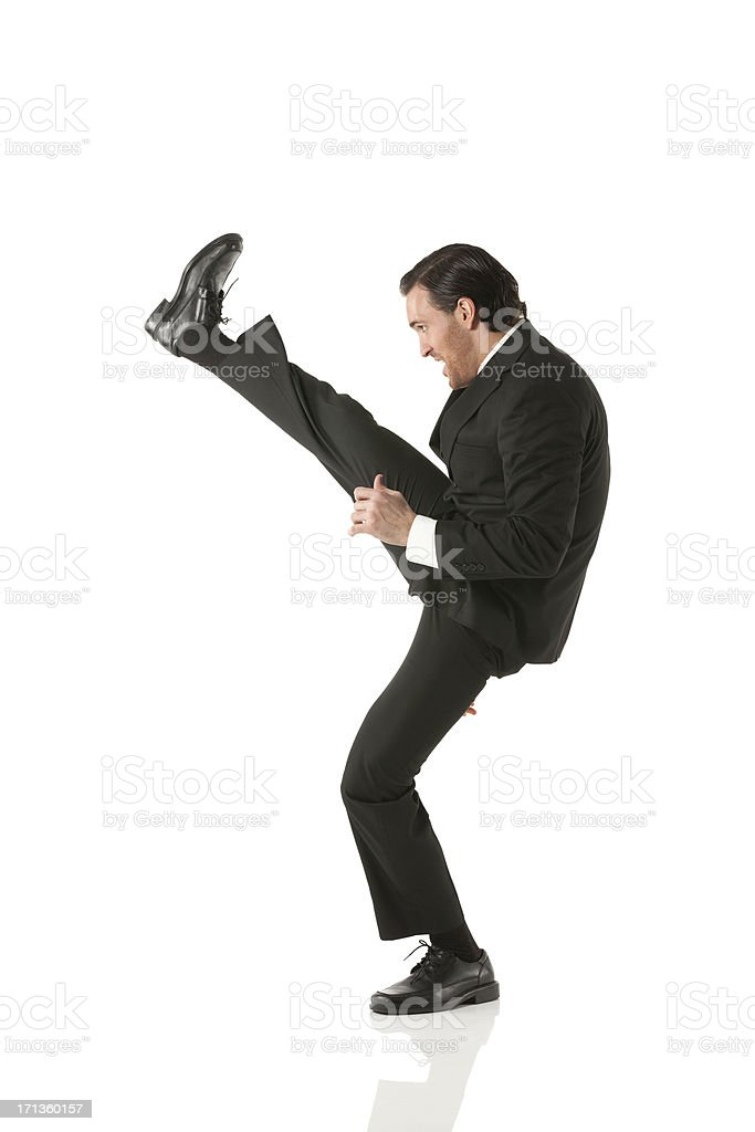 Businessman kicking stock photo