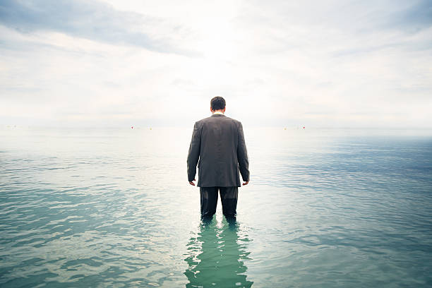 businessman knee-deep in water businessman is knee-deep in water wading stock pictures, royalty-free photos & images