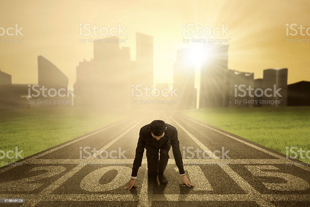 Businessman kneeling on track Man kneeling on track and ready to chase his dream in the future 2015 2015 Stock Photo