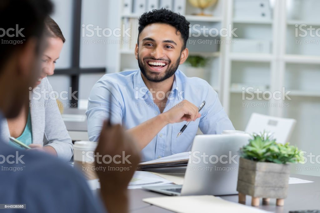 Businessman laughs while meeting with colleagues stock photo