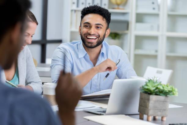 businessman laughs while meeting with colleagues - popolazione indiana foto e immagini stock