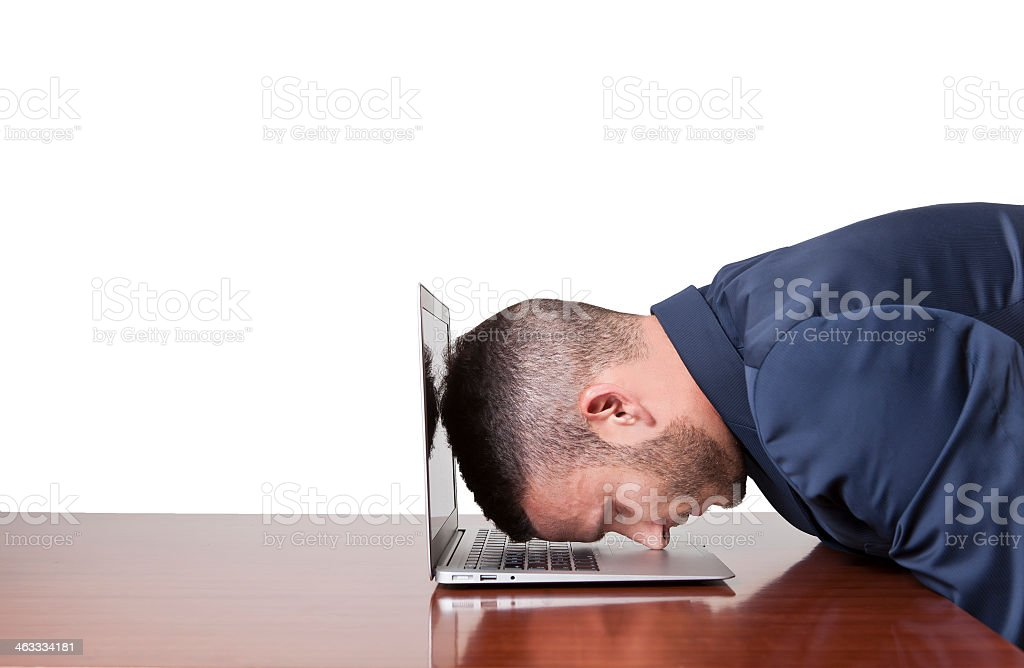 Businessman laying his head down on his laptop stock photo