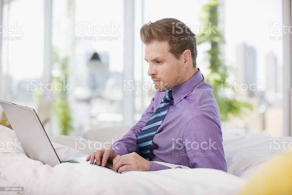 Businessman laying in bed typing on laptop royalty-free stock photo