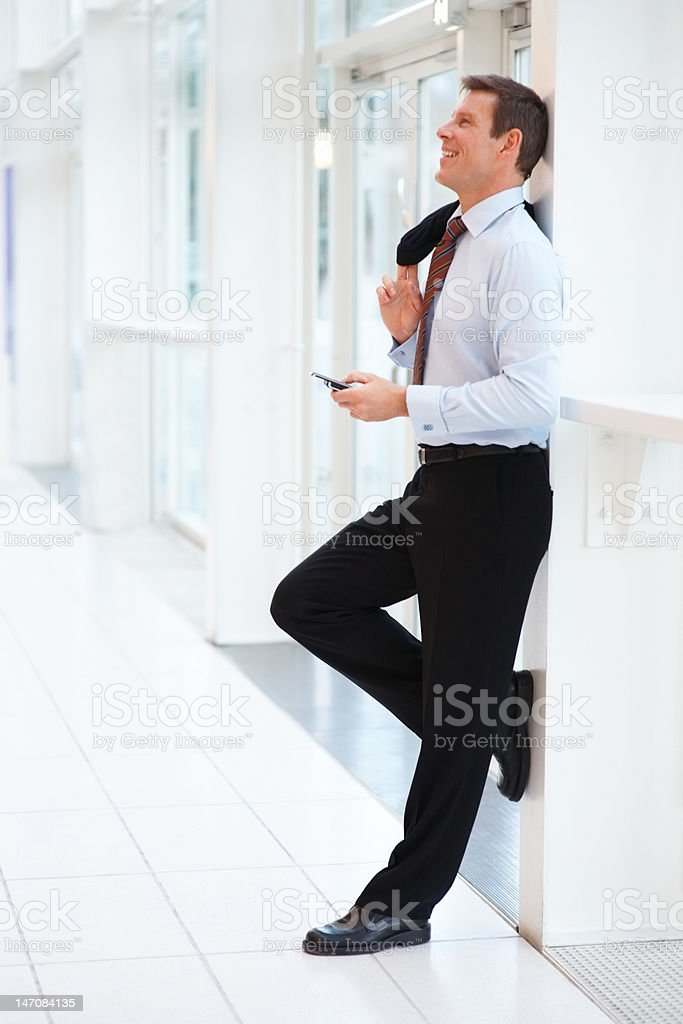 Businessman leaning against wall and holding a cellphone royalty-free stock photo