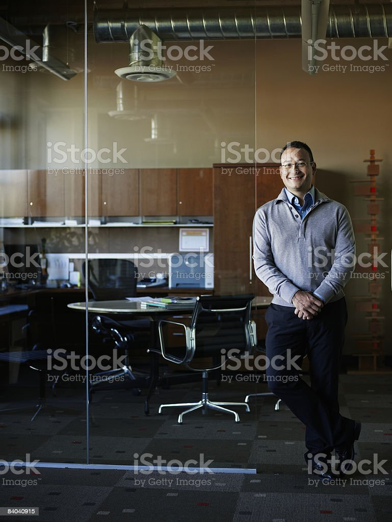 Businessman leaning against wall of office foto de stock libre de derechos