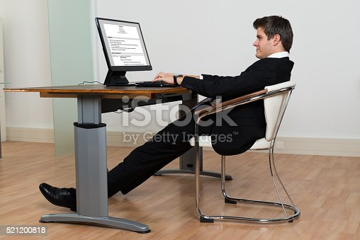 Businessman Leaning Back In His Chair While Working On