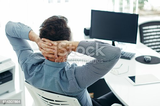 istock Businessman leaning back in the chair 614307864