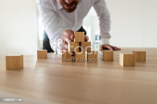 istock Businessman leaning in to carefully assemble pyramid shape with blank wooden blocks 1066557146