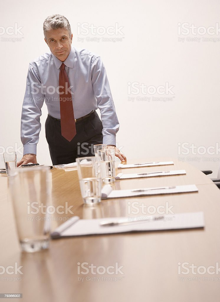 Businessman leaning on boardroom table looking at camera royalty-free stock photo