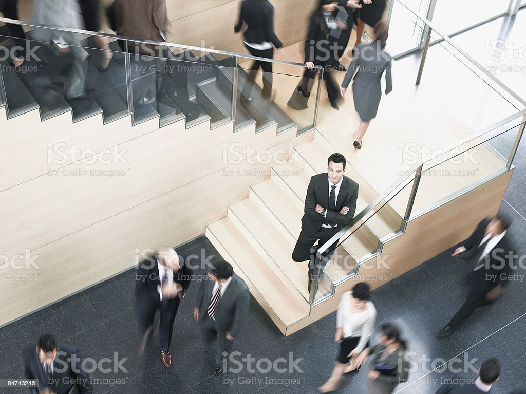 Businessman leaning on busy office staircase royalty-free stock photo