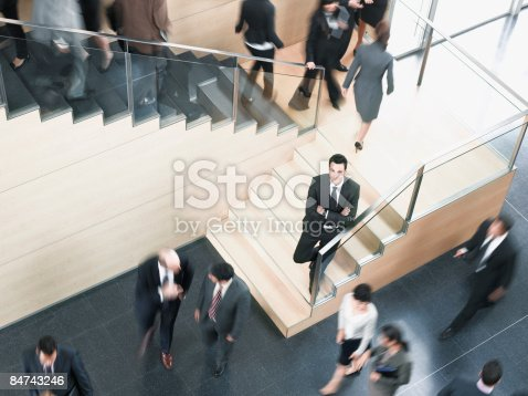 483635979 istock photo Businessman leaning on busy office staircase 84743246