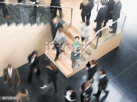 483635979 istock photo Businessman leaning on busy office staircase 84743249
