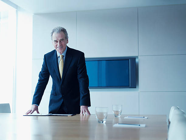 Businessman leaning on conference room table stock photo
