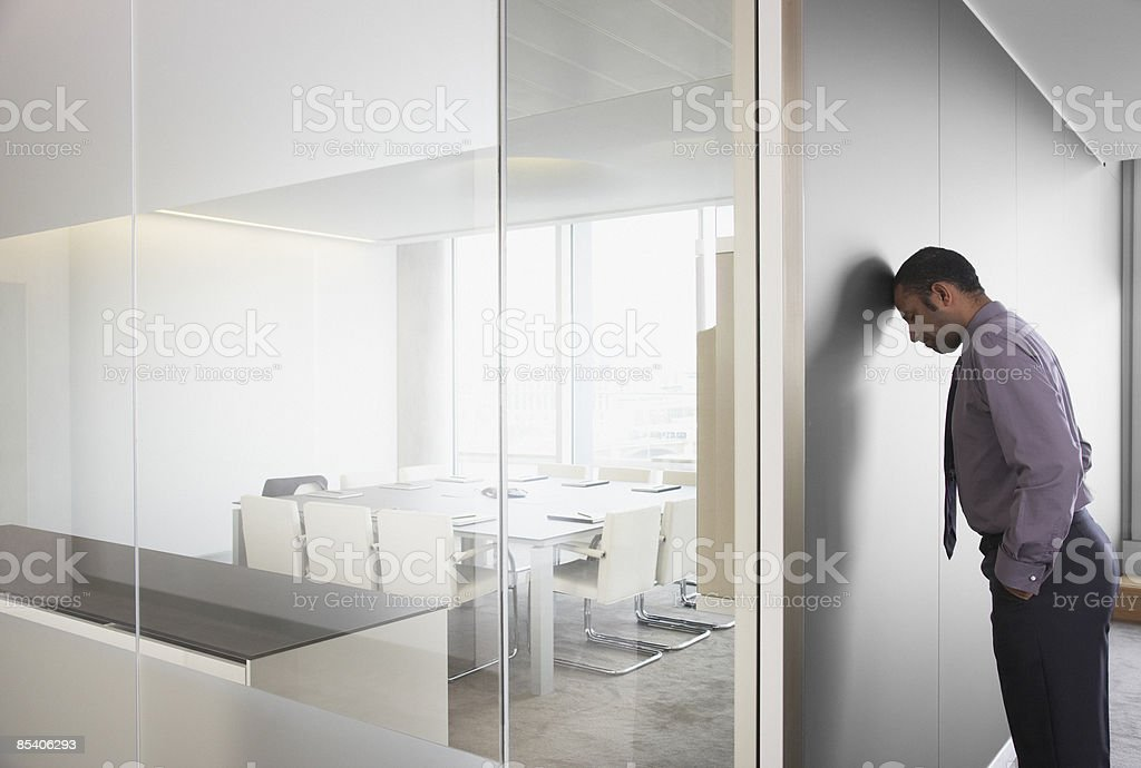 Businessman leaning on corridor wall royalty-free stock photo
