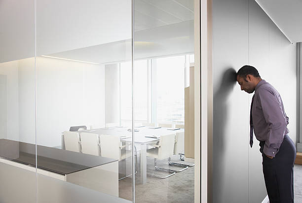 Businessman leaning on corridor wall stock photo