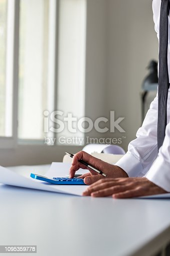 istock Businessman leaning on his office desk using calculator 1095359778