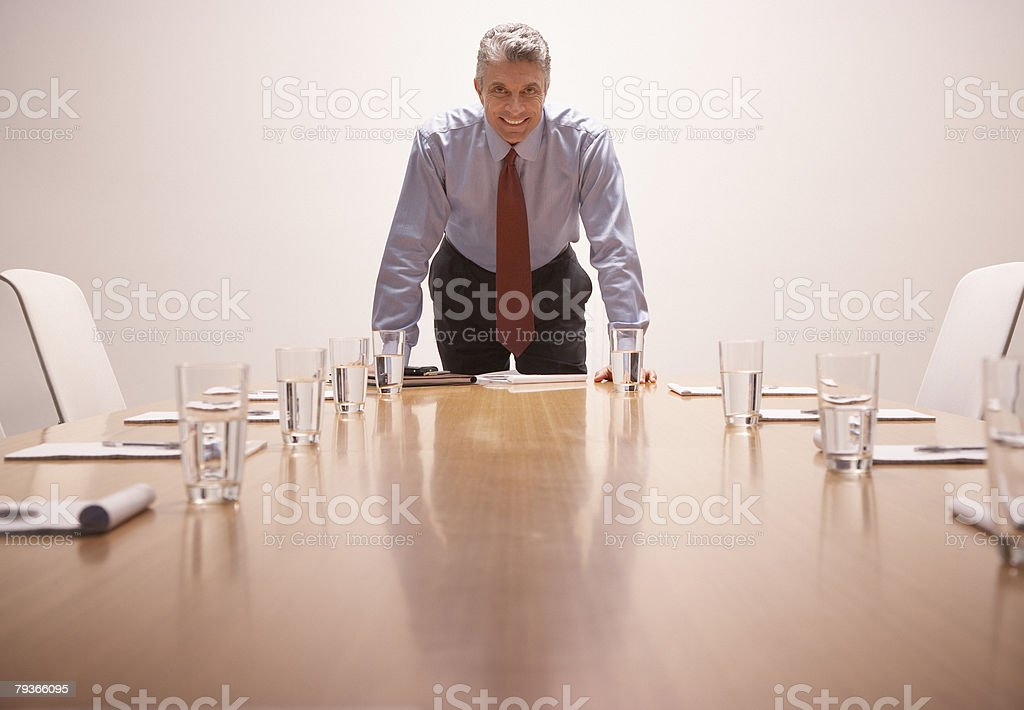 Businessman leaning on table in boardroom looking at camera 免版稅 stock photo