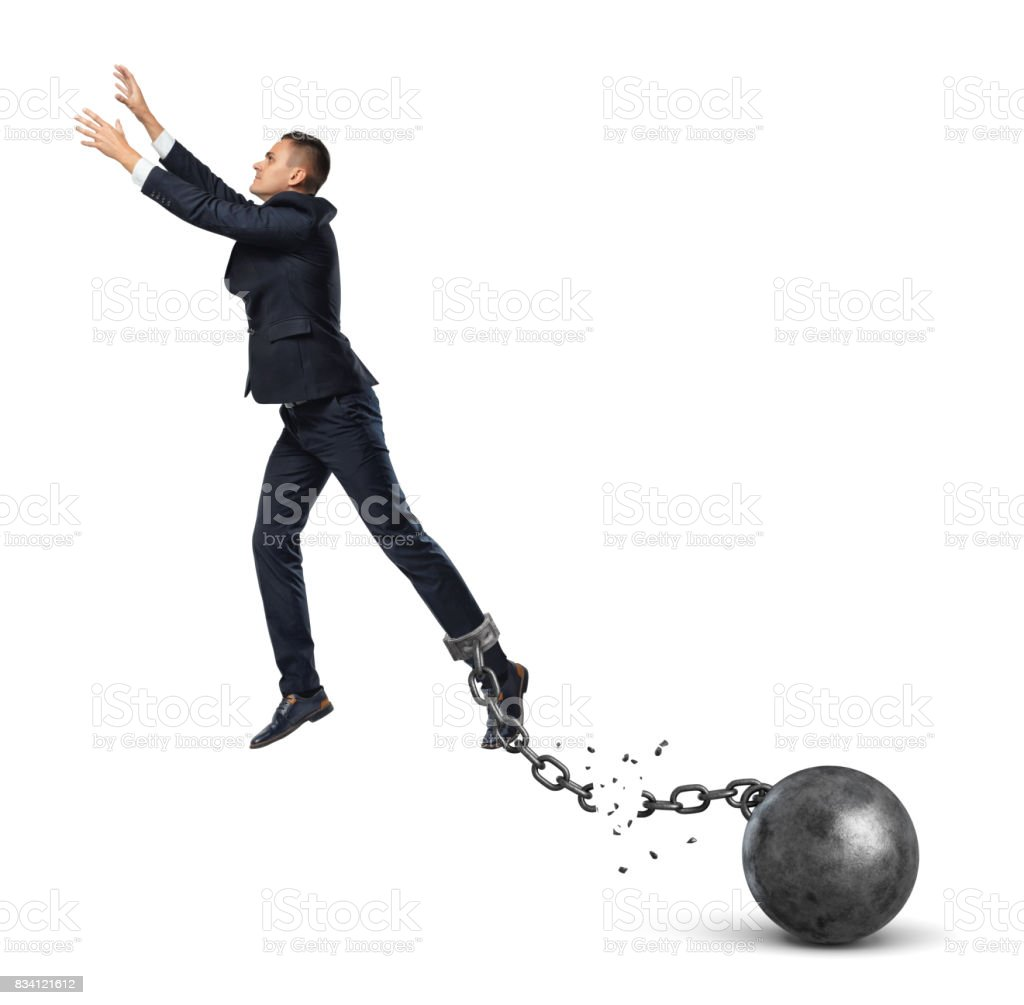 A businessman leaping away from an attached iron ball with a broken chain stock photo