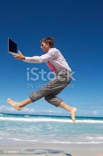 istock Businessman Leaps Along Shore w Laptop 157686923