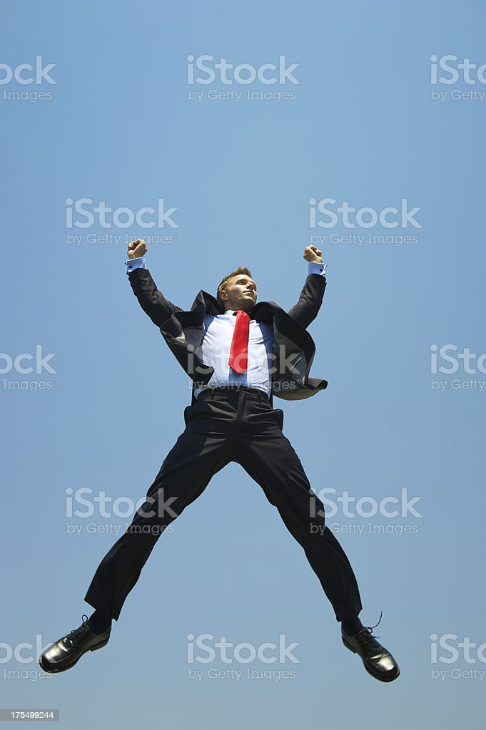 Businessman Leaps into Blue Sky with Arms Raised stock photo